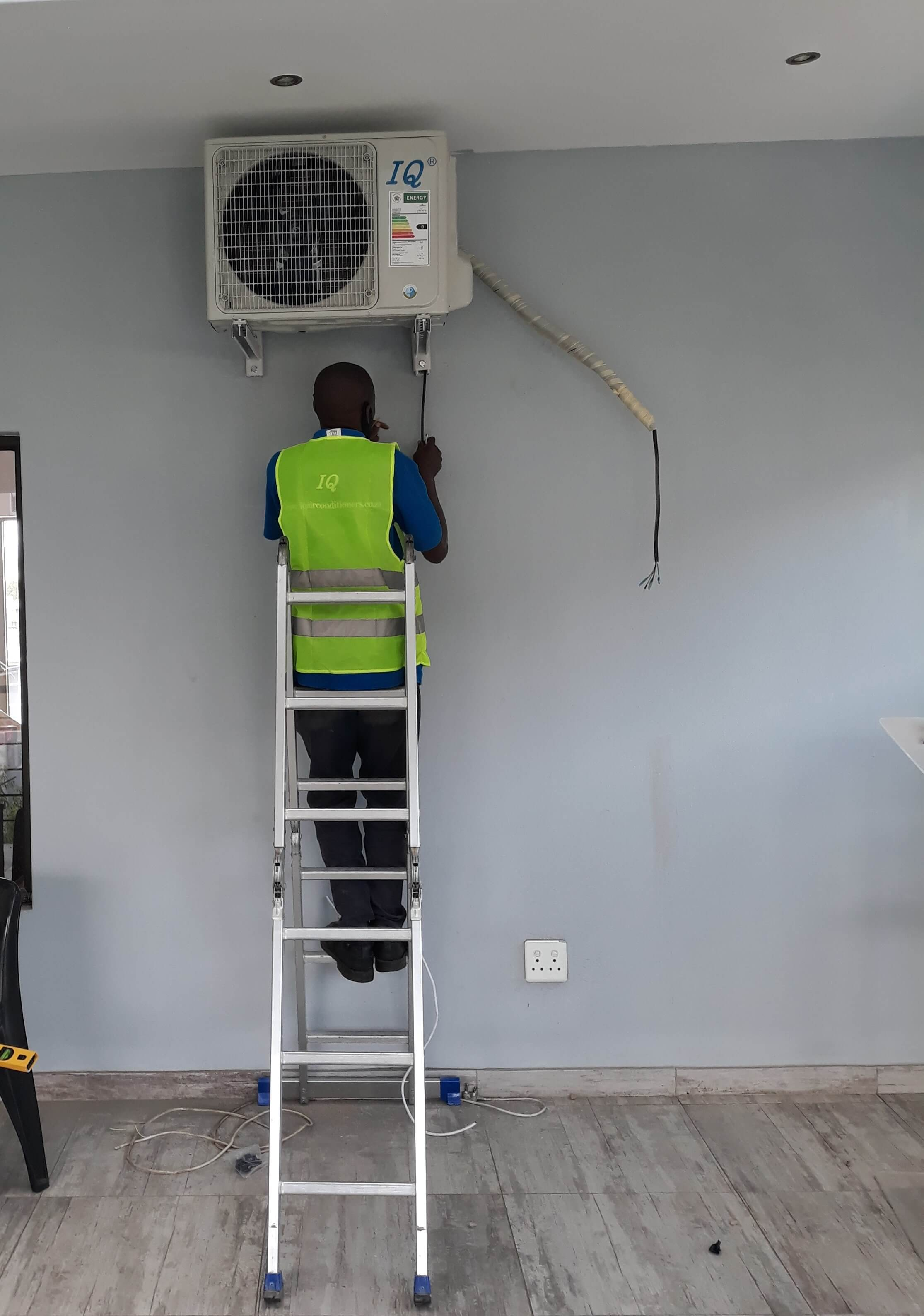 air conditioning technician installing home ac unit